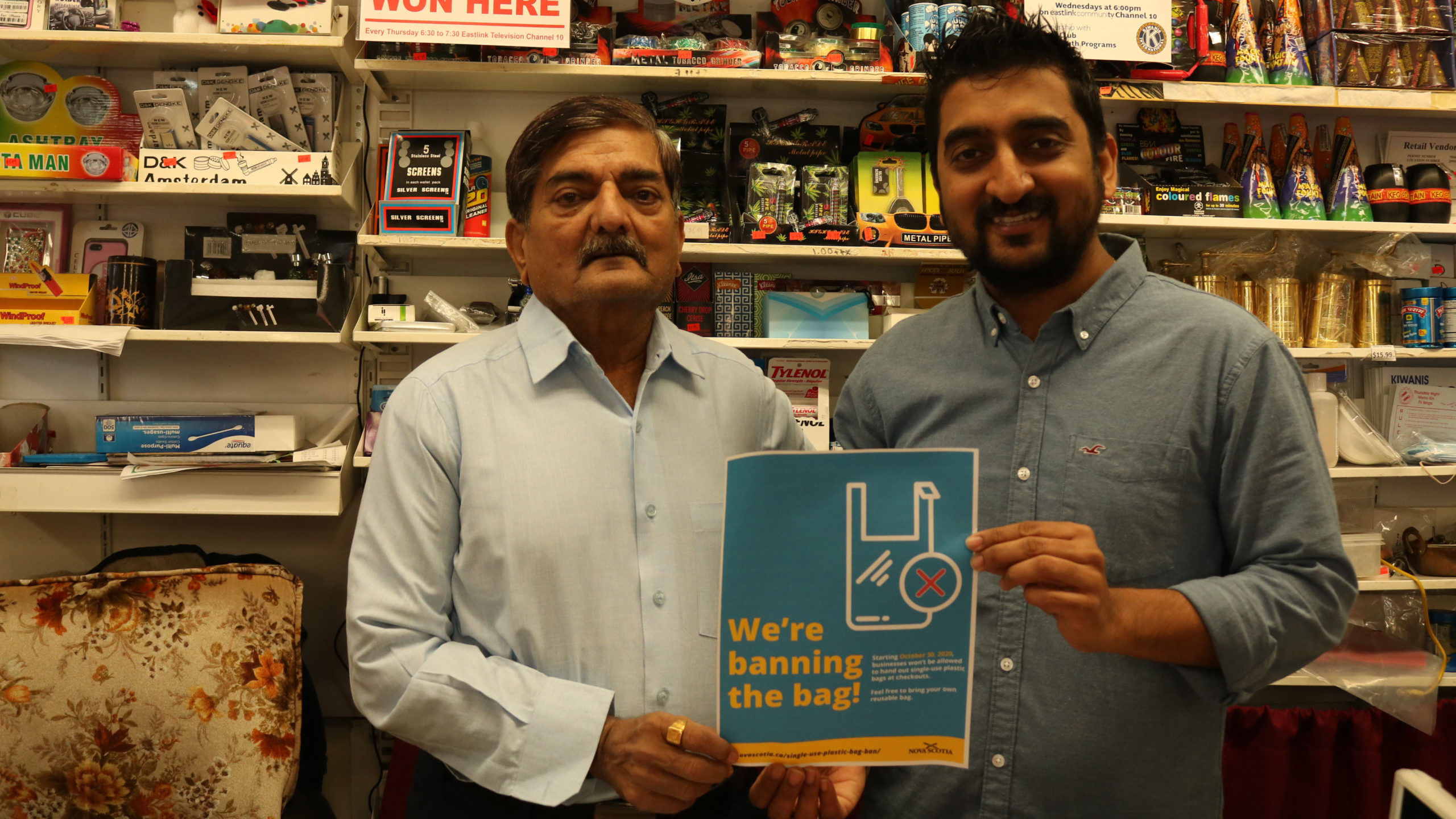 Krunal Shah and his dad pose with a government poster he says helped communicate the new rules to customers