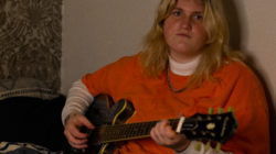 Em Burry sits on their bed while holding their guitar. They are a young artist carving their path in a shaken industry.