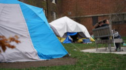 An image of two tents in Grange Park behind a two people seated on a bench