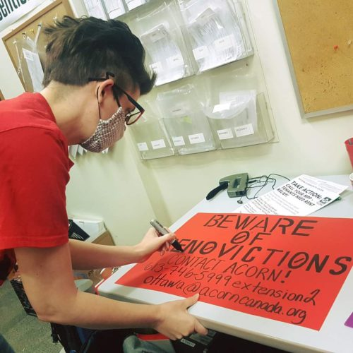 Photo of a woman in a red T-shirt drawing a sign