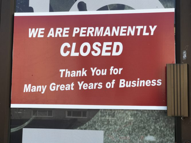 Photo of a sign on a door that says permanently closed for business