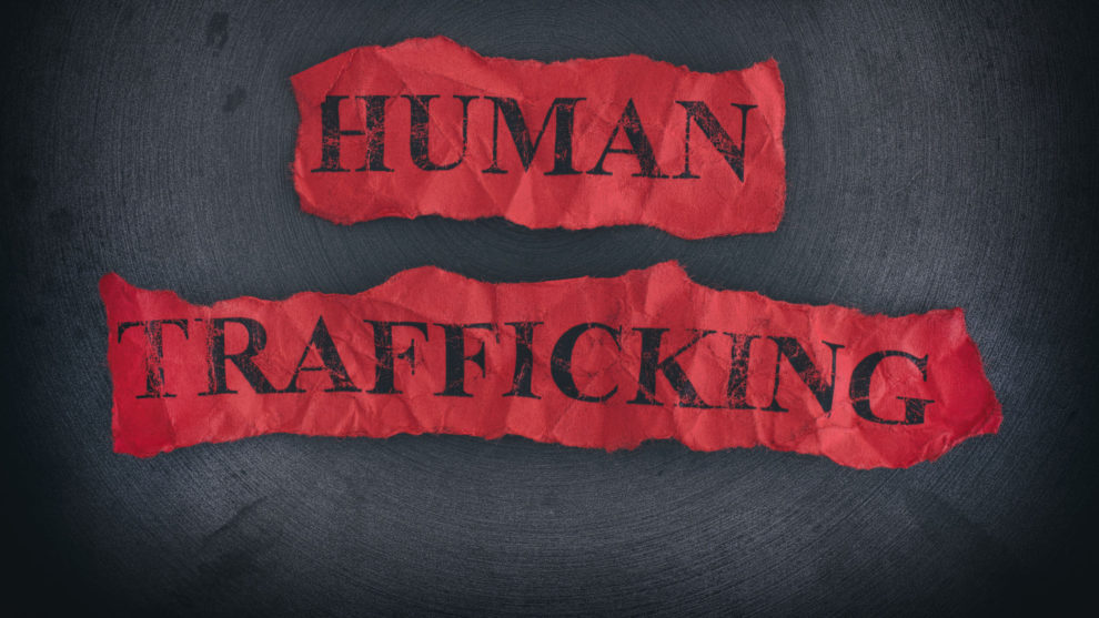 Crumpled pieces of paper with the words Human Trafficking.